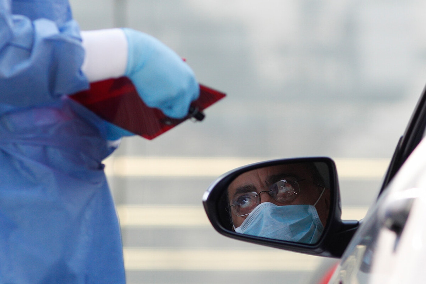 doctor taking down information from man wearing a mask in a car