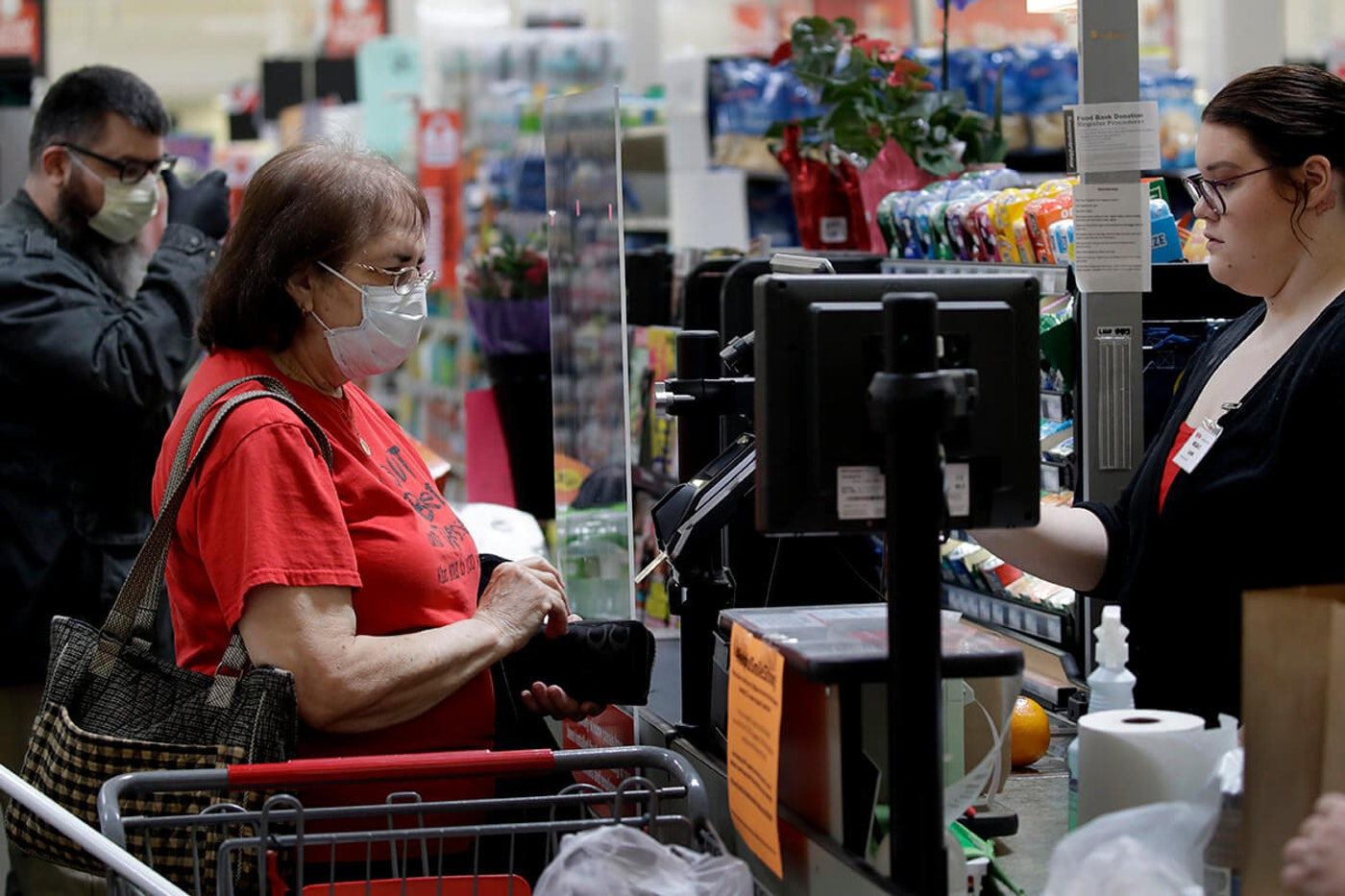 A woman checks out at the grocery store while wearing a mask.