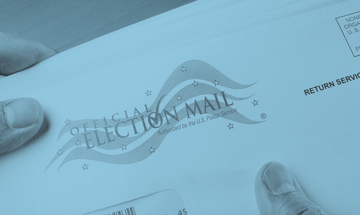 hand holding mail-in ballot