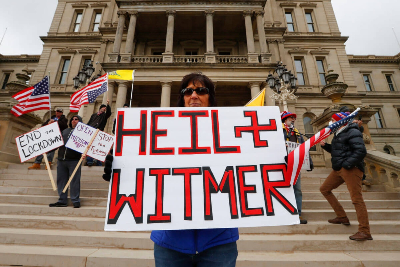 Dawn Perreca protest in Lansing, Mich., Wednesday, April 15, 2020. Flag-waving, honking protesters drove past the Michigan Capitol on Wednesday to show their displeasure with Gov. Gretchen Whitmer's orders to keep people at home and businesses locked during the new coronavirus COVID-19 outbreak. (AP Photo/Paul Sancya)