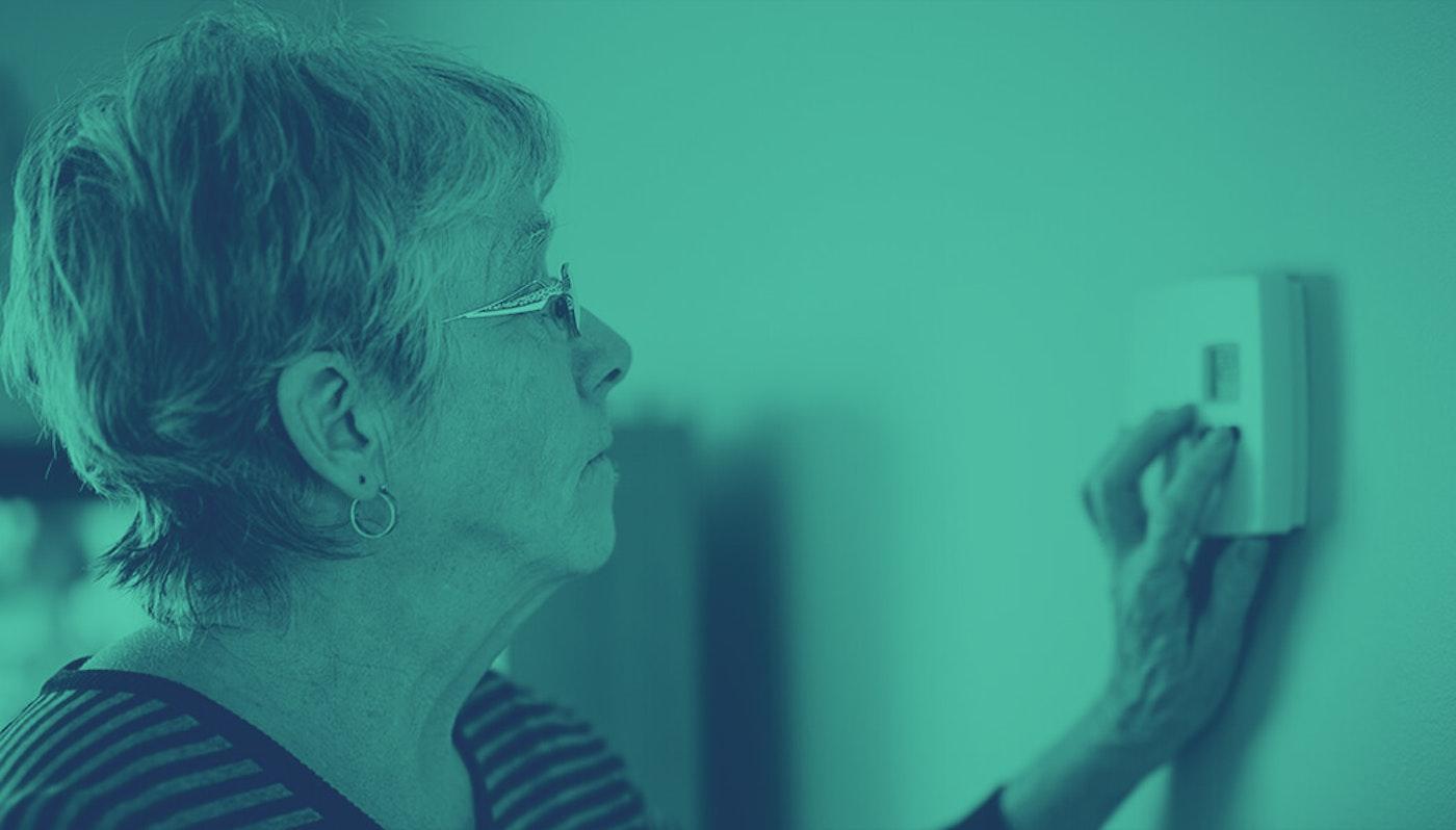 senior woman adjusting thermostat on wall