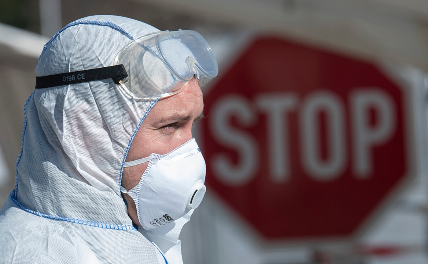 person in protective medical gear in front of a stop sign