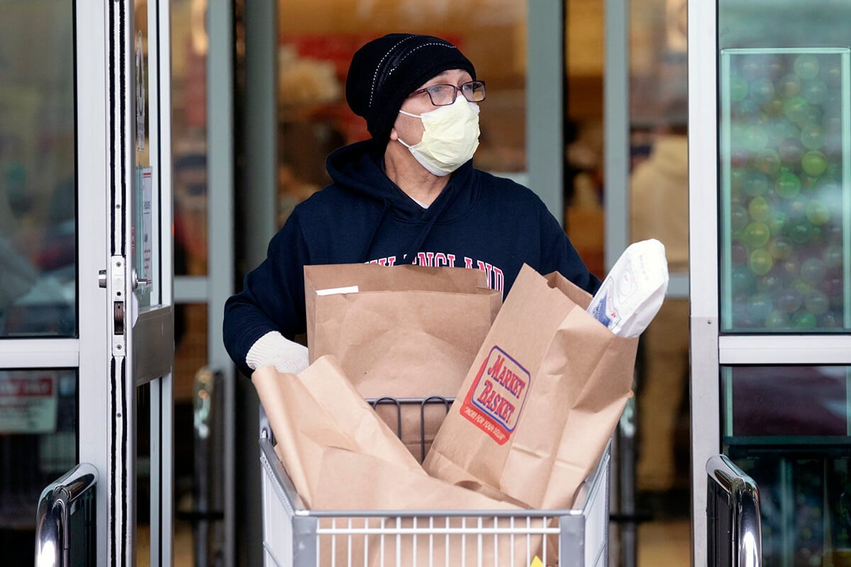 man wearing mask using shopping cart full of groceries