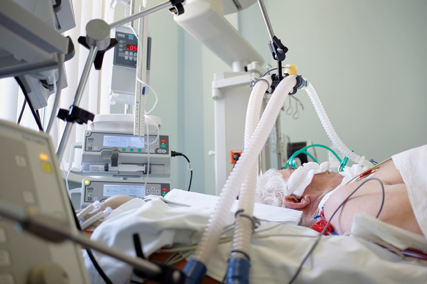elderly man in hospital bed hooked up to ventilator