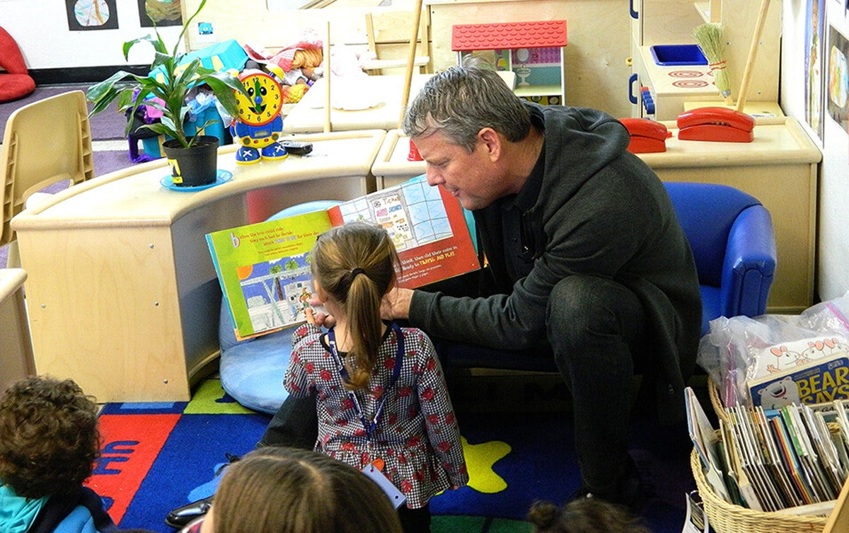 man reading book to three children