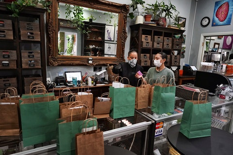 two dispensary employees wearing masks filling paper bags with orders