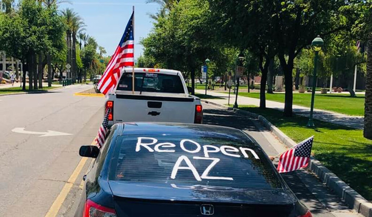 "truck and car part of protest, car's back windshield reads ""Reopen AZ"""