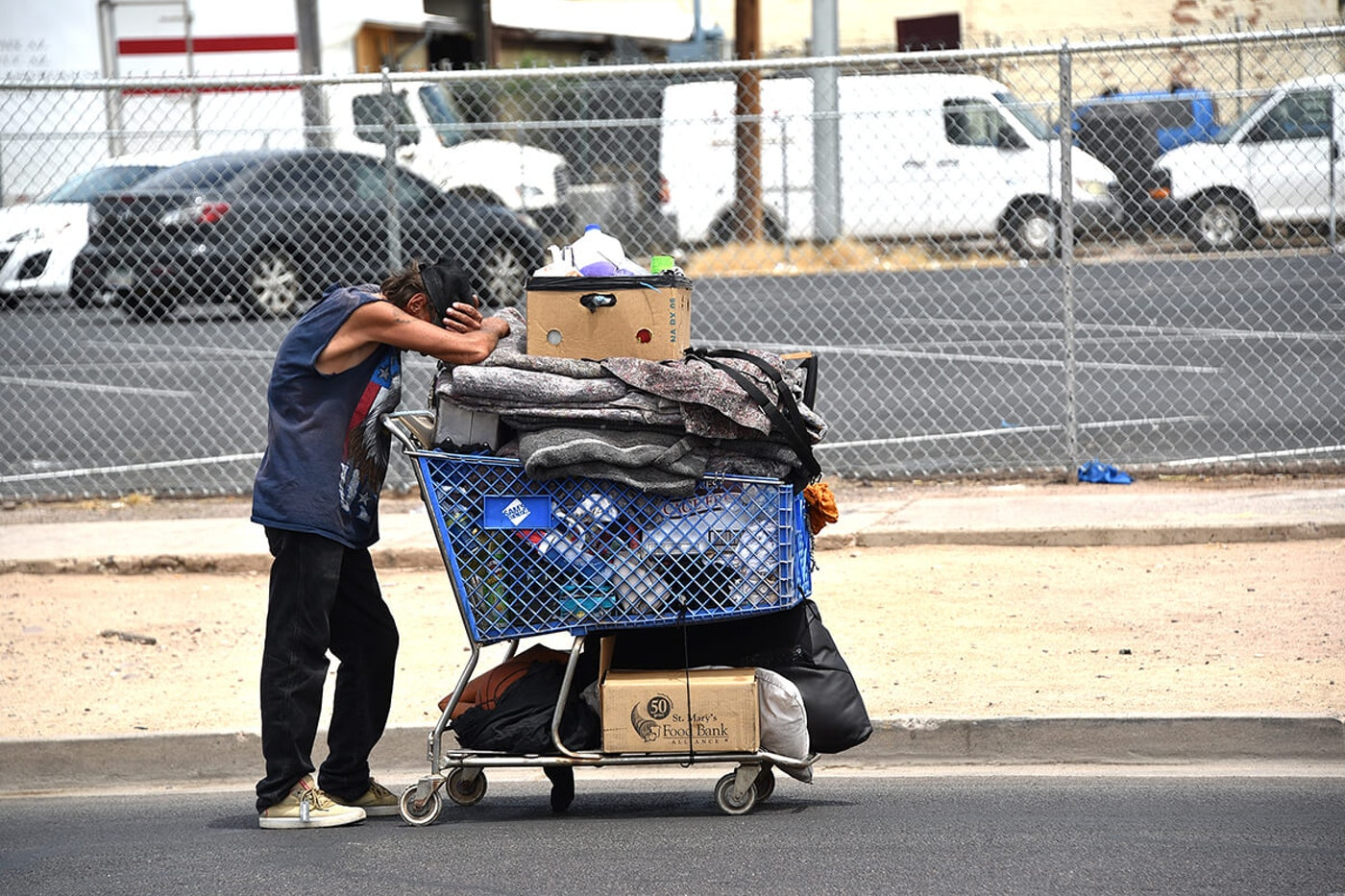 homeless man leaning on shopping cart full of items