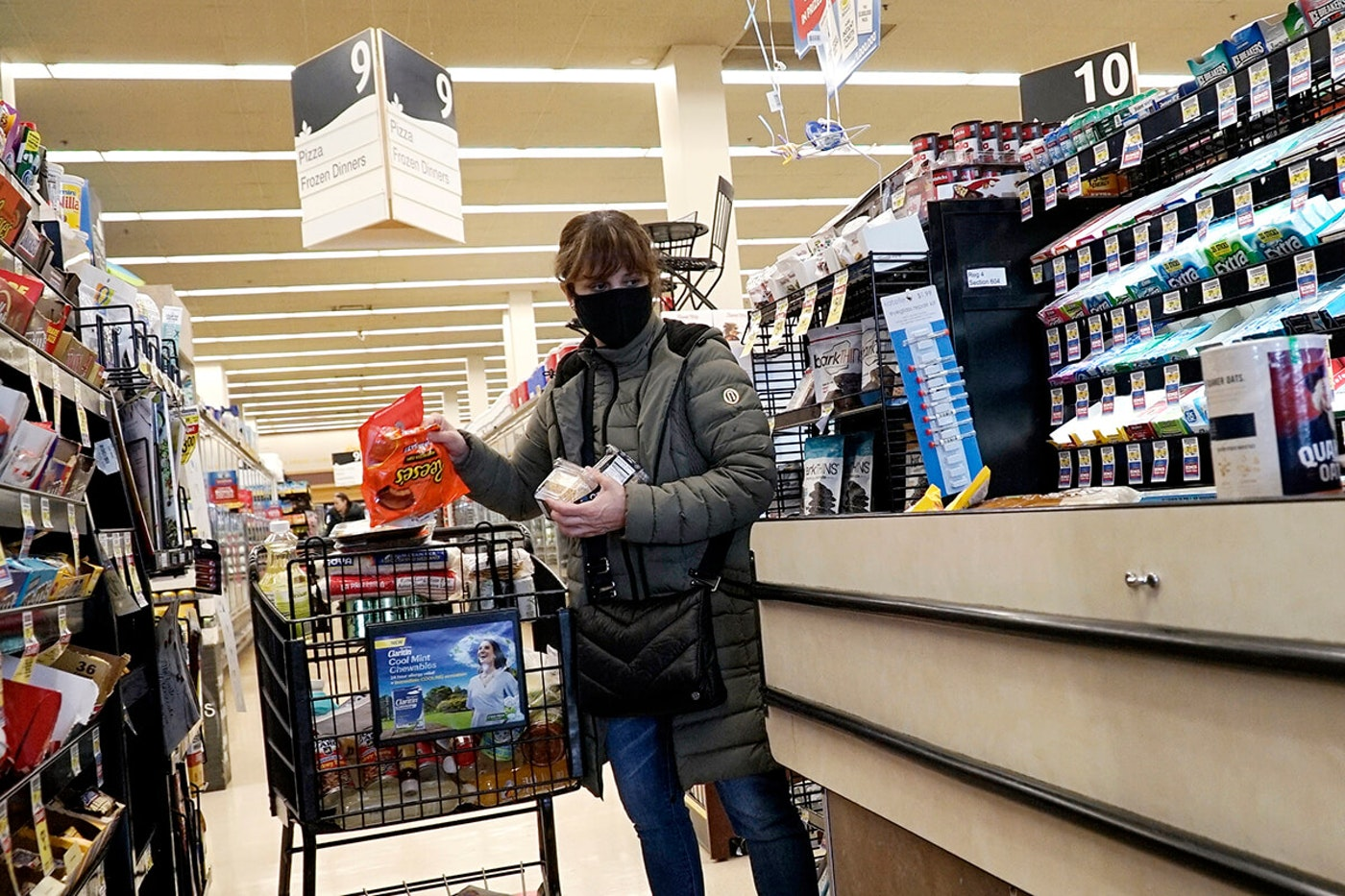 masked shopper loading groceries onto cashier's belt
