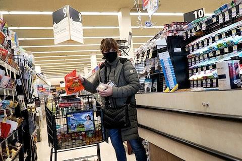 masked shopper loading groceries onto cashier's belt