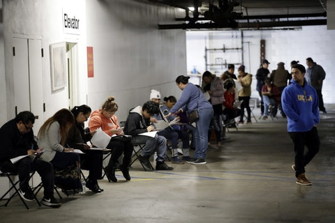 FILE - In this March 13, 2020 file photo, unionized hospitality workers wait in line in a basement garage to apply for unemployment benefits at the Hospitality Training Academy in Los Angeles.    (AP Photo/Marcio Jose Sanchez, File)