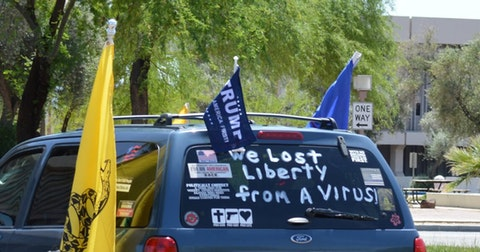 "car with ""we lost liberty to a virus"" written on back windshield"