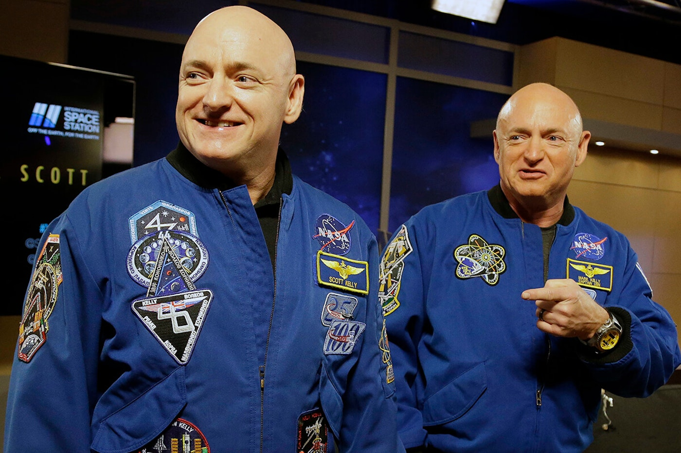 Scott and Mark Kelly standing next to each other wearing spacesuits