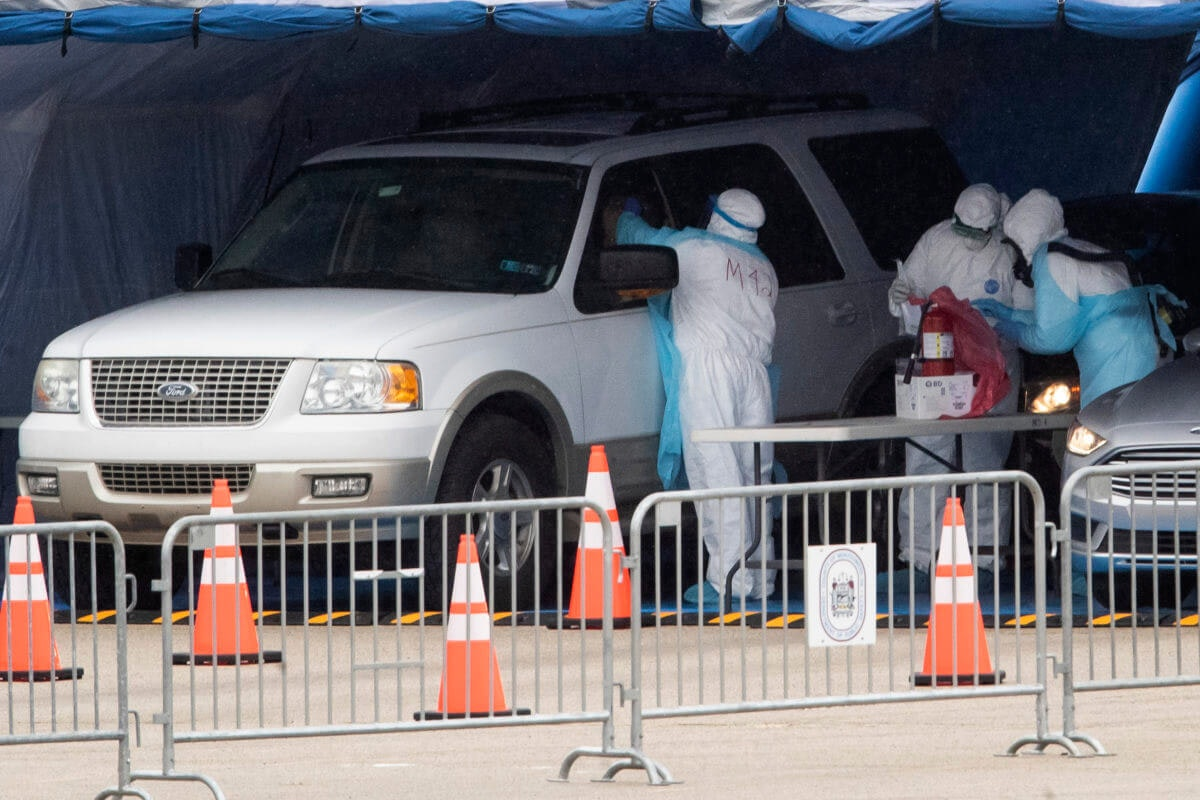 Medical workers perform a coronavirus test on driver at the Temple University Ambler campus in Ambler, Pa., Wednesday, March 25, 2020. (AP Photo/Matt Rourke)