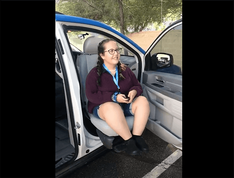 14-year-old girl sitting on motorized transport chair connected to SUV
