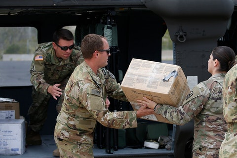 Three National Guard members unloading boxes from helicopter