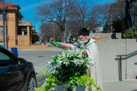 FILE -  In this Saturday, April 11, 2020 file photo, Rev. Timothy Pelc blesses Easter baskets outside St. Ambrose Church in Grosse Pointe Park, Mich. Pelc, wearing church vestments and protective gear, offered a prayer and sprayed holy water from a squirt gun instead of blessing baskets inside the church in a bid to maintain social distancing during the coronavirus pandemic. (Natalie White via AP)