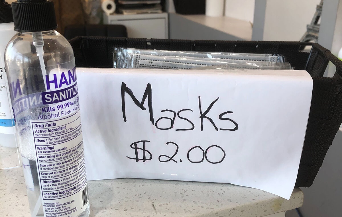 hand sanitizer and sign selling masks for $2