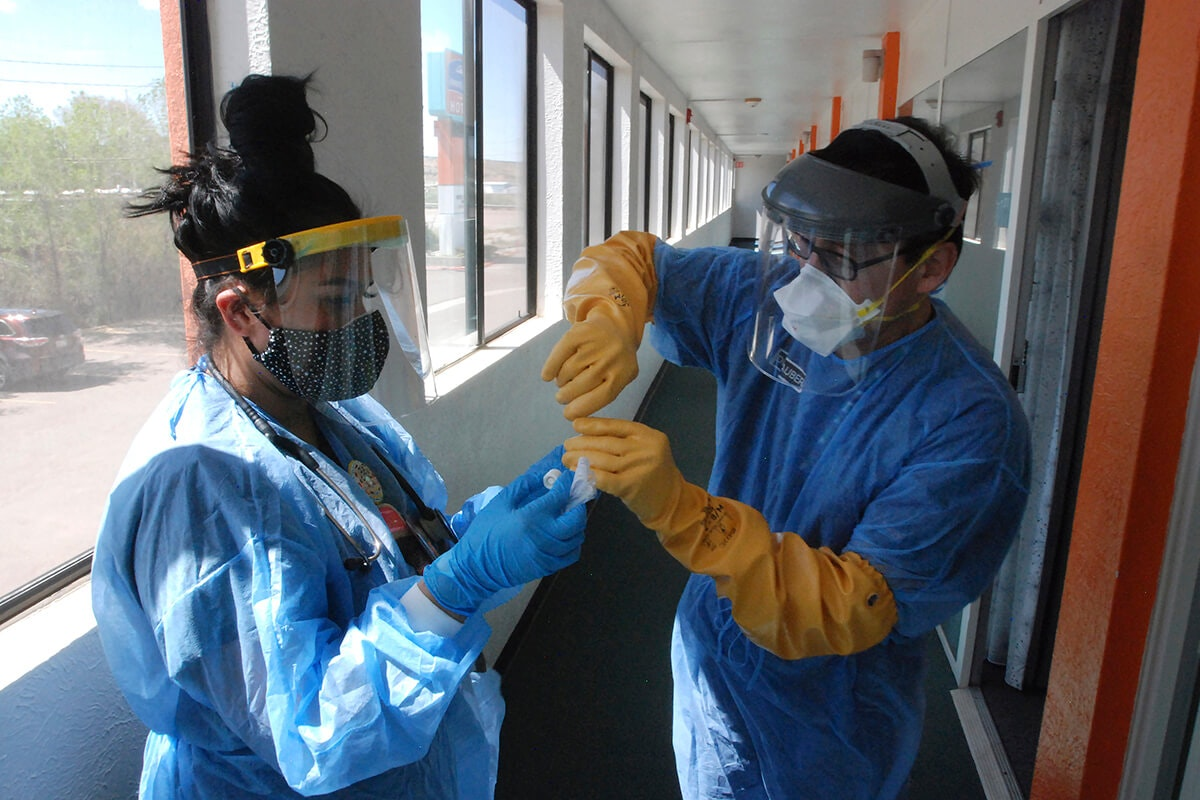 two healthcare workers dressed in smocks and masks test a coronavirus test sample