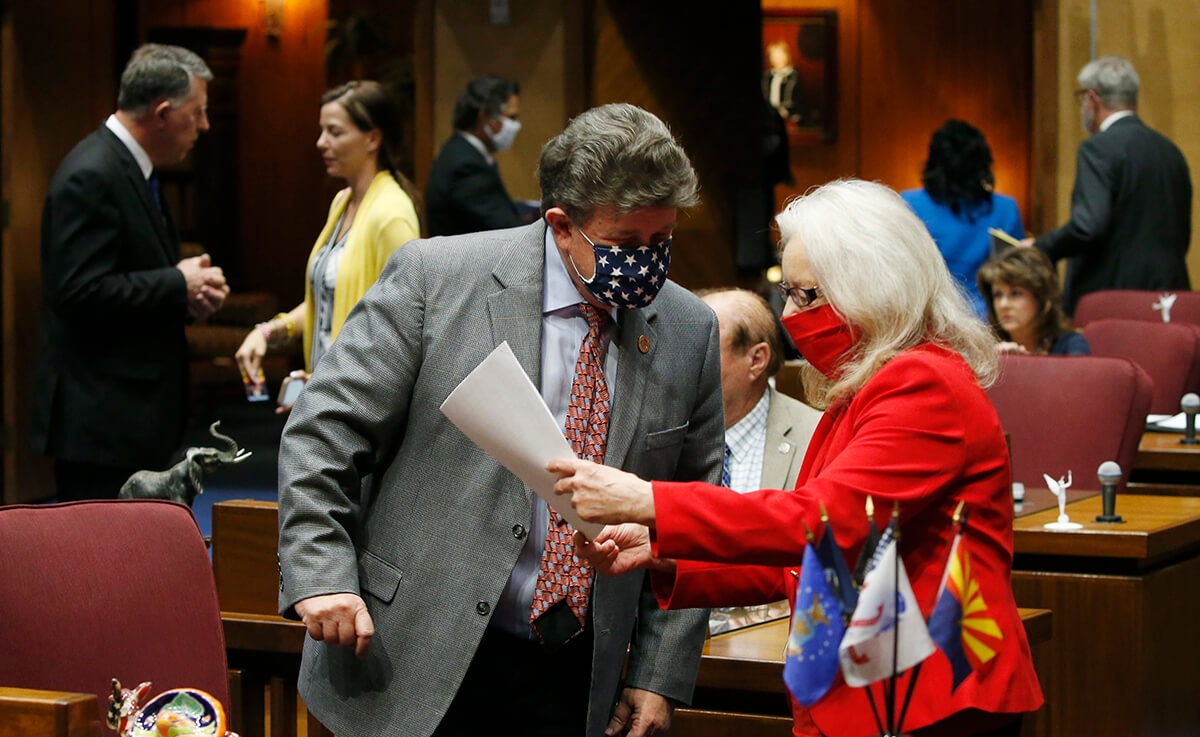 man and woman speak to each other in Arizona House with masks on