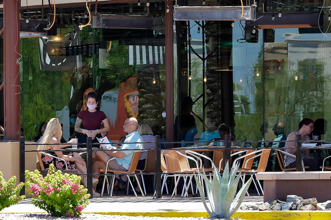 two people sitting at table at restaurant while waitress in mask speaks with them
