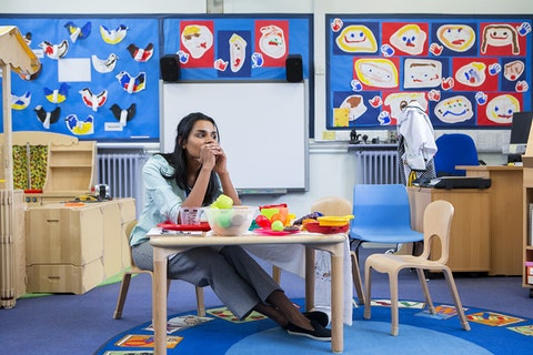 woman sitting alone at desk in preschool classroom
