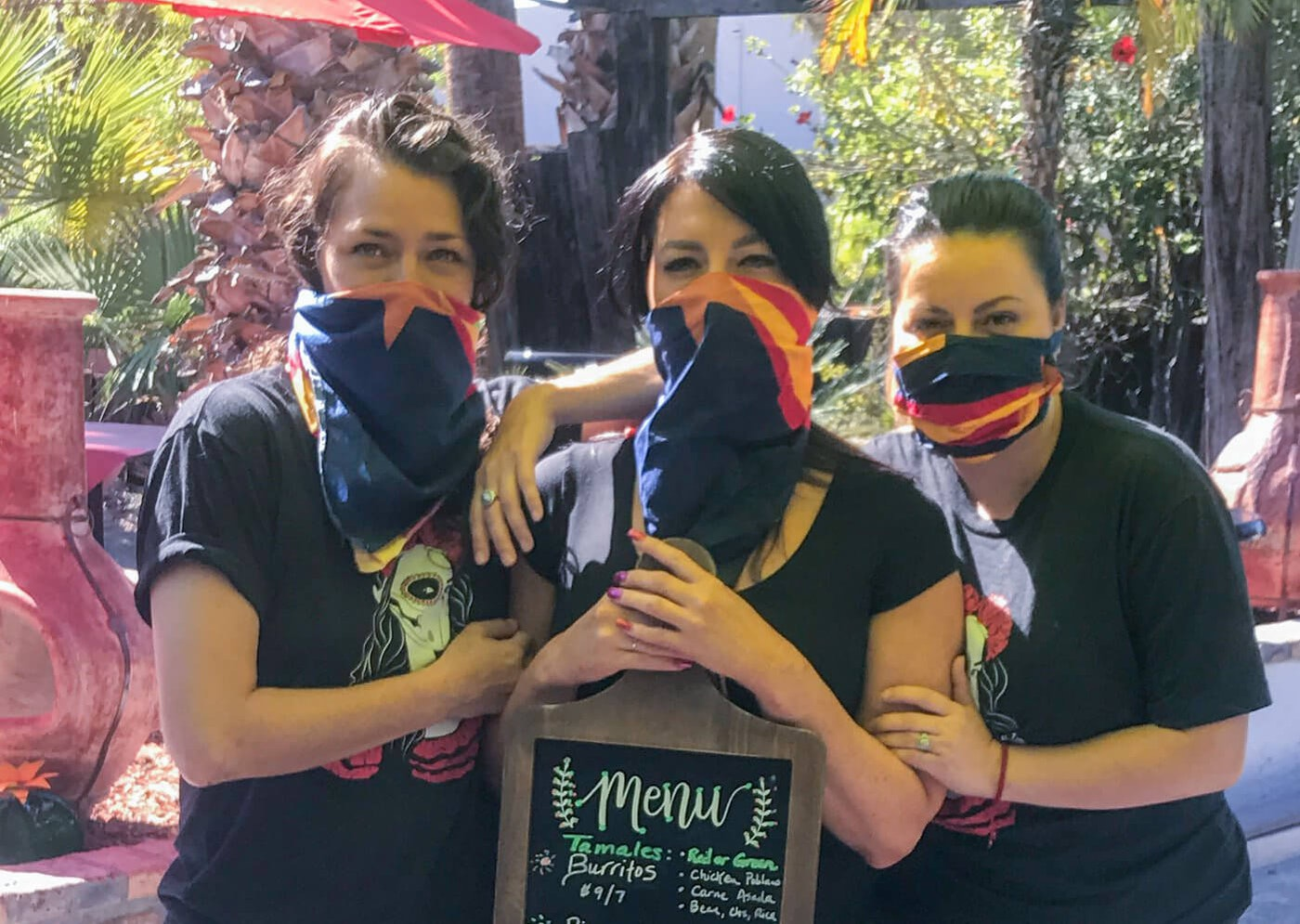 three women wearing face masks holding a menu
