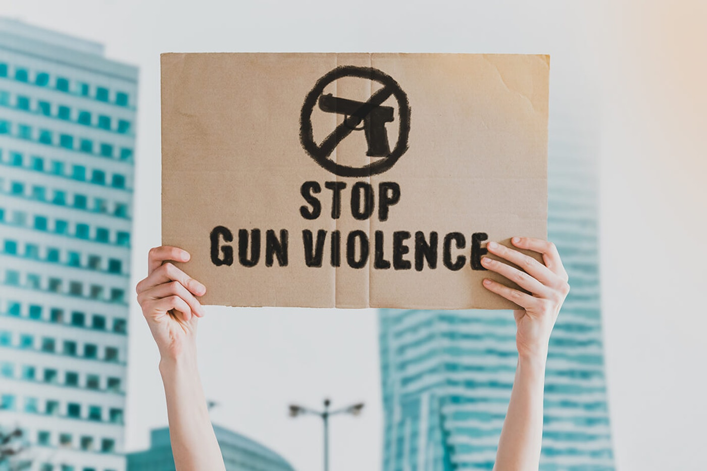 """person holding sign that says """"stop gun violence"""""""