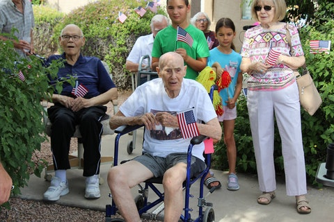 Chuck Shuff sitting outside in wheelchair holding American flag