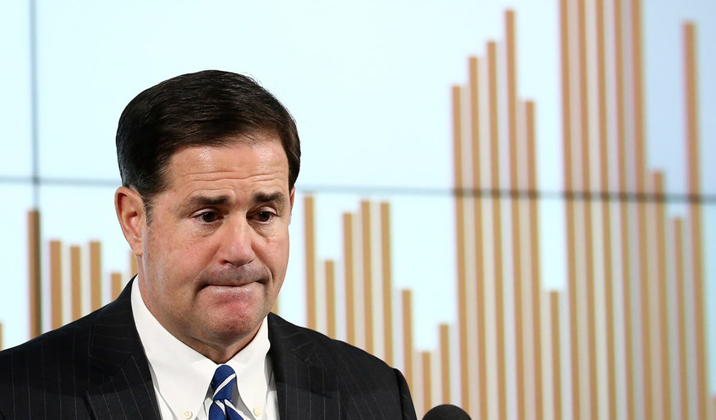 Gov. Ducey in front of a bar graph