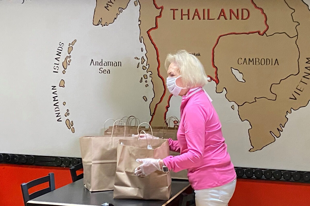 Malee's owner Deirdre wearing mask and gloves packing bags