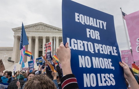 person holding sign calling for LGBTQ rights in crowd outside of Supreme Court