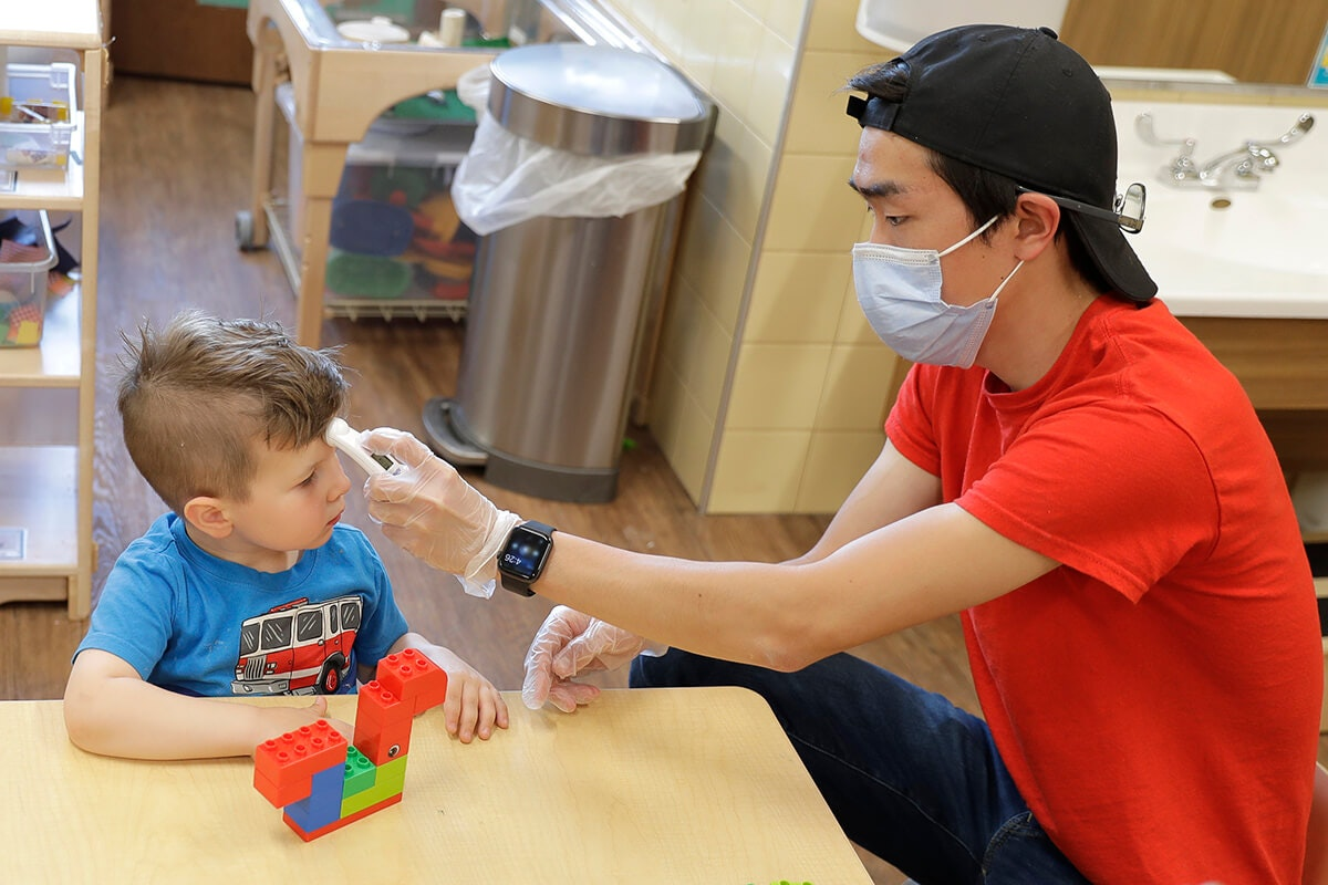 man holds thermometer up to young boy's forehead at childcare center