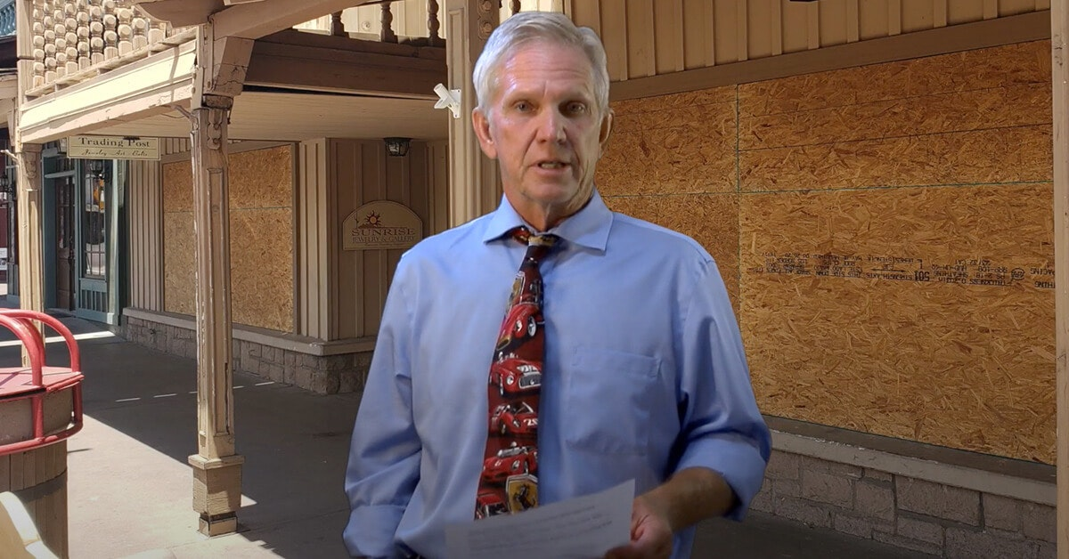 Guy Phillips standing in front of boarded-up businesses