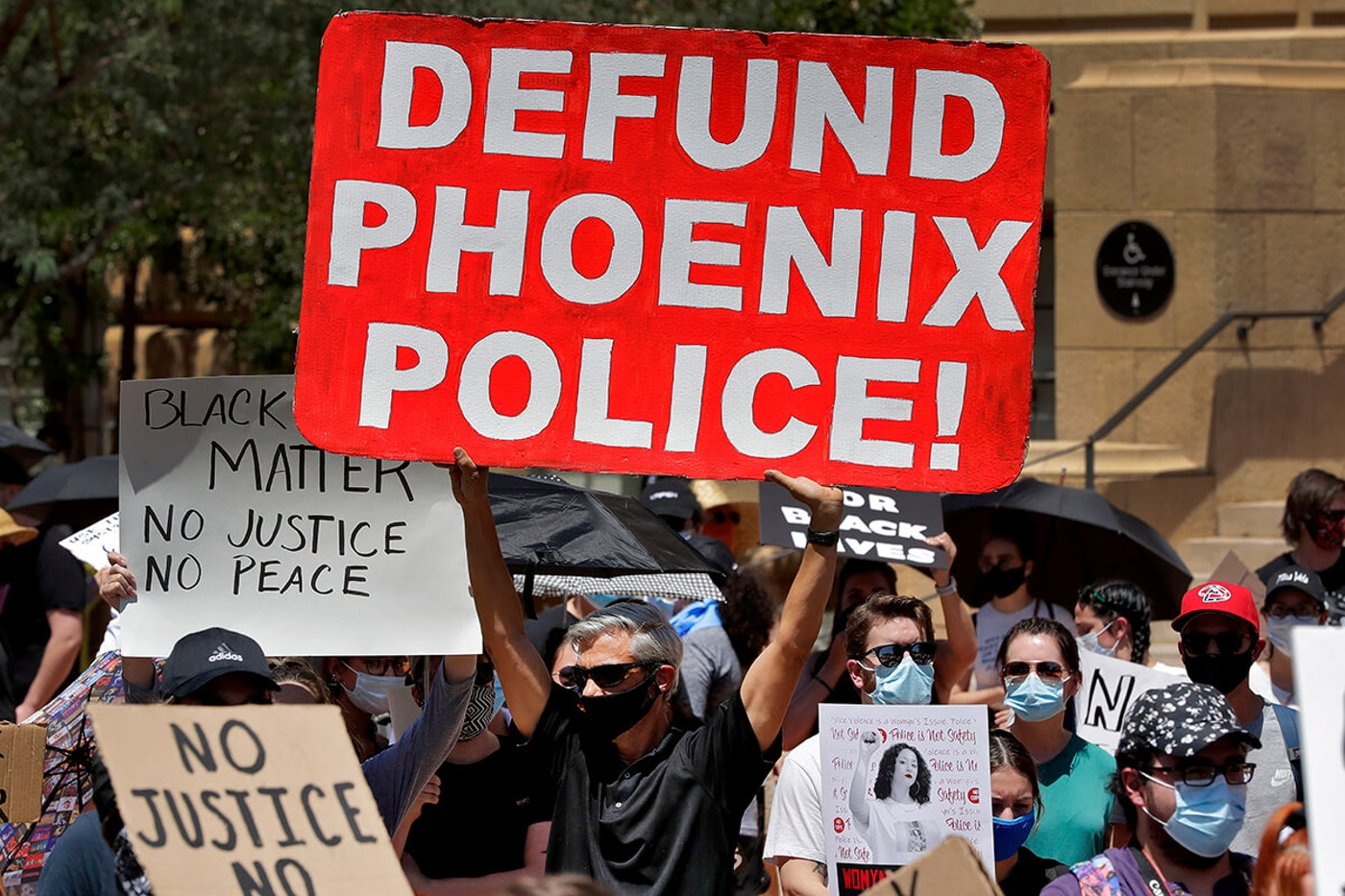 "protester holding sign that says ""Defund Phoenix Police"""