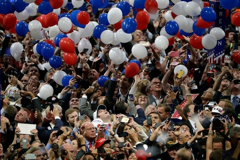large crowd of people cheering as red, white and blue balloons fall