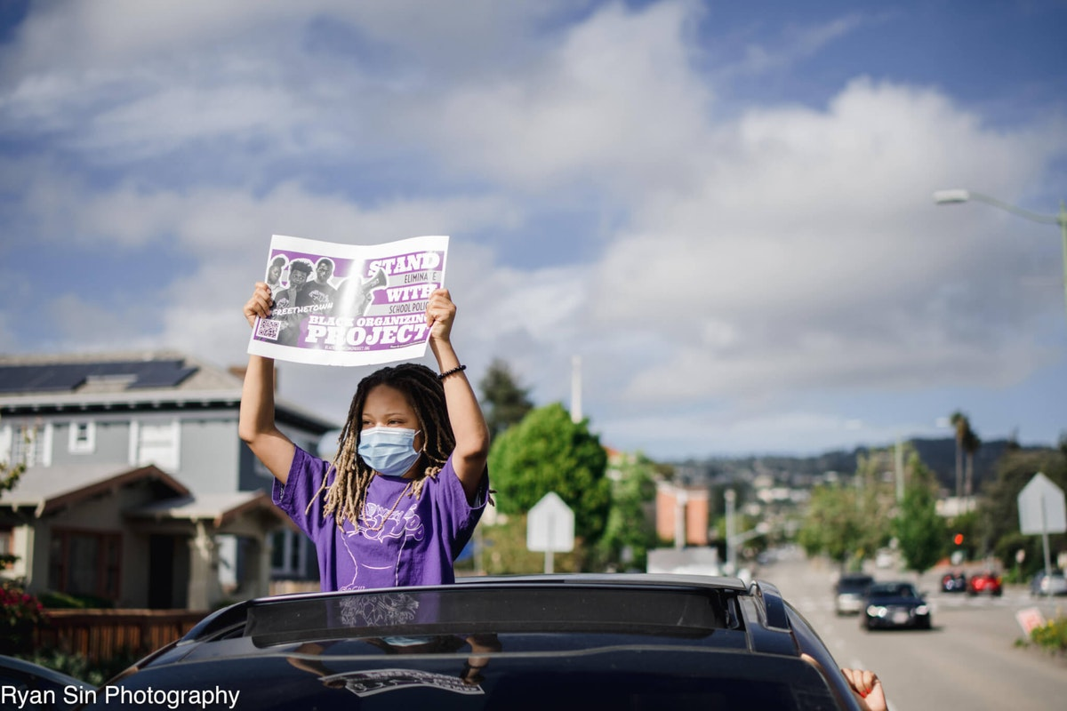 Black Organizing Project Youth Leader Imani Snodgrass advocating for equal rights during their car caravan in early June. Community members visited the homes of Oakland school board members to urge them to support removing police from schools. (Photo courtesy of Ryan Sin Photography/Black Organizing Project)