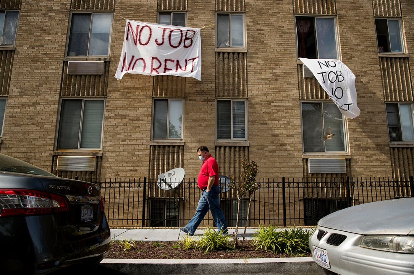 "man walking past apartment buildings, which has signs posted on it saying ""no job no rent"""