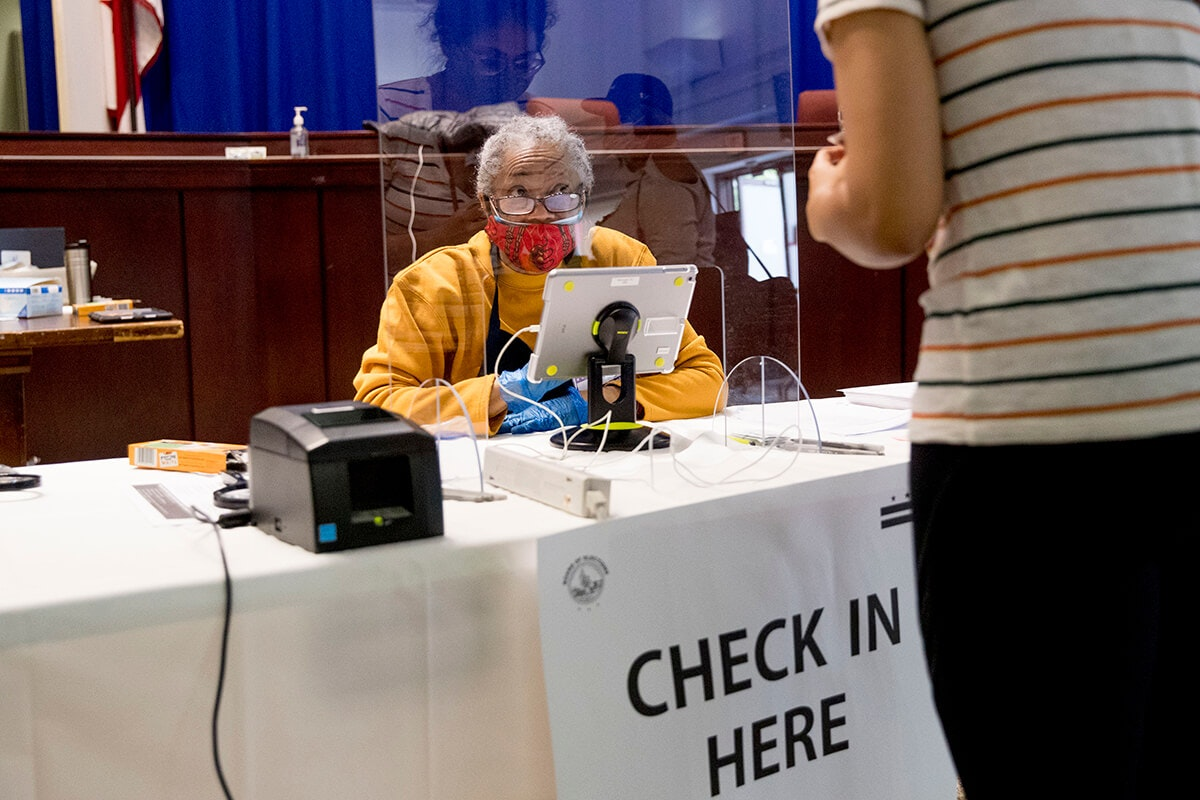 older poll workers sits behind plastic shield at check-in table wearing protective equipment