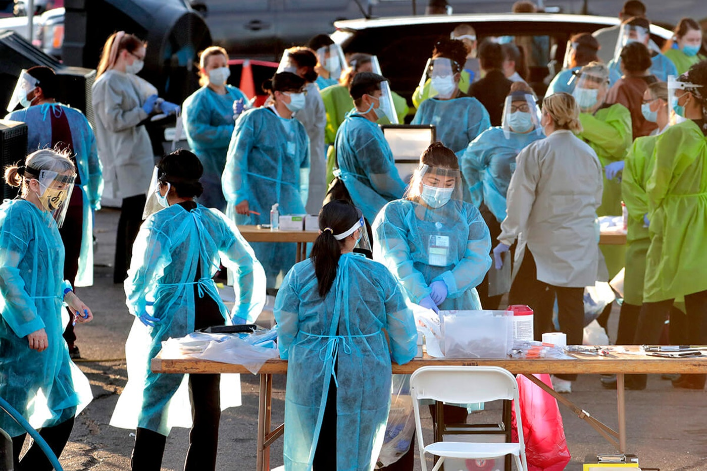 crowd of medical professionals wearing PPE working outside