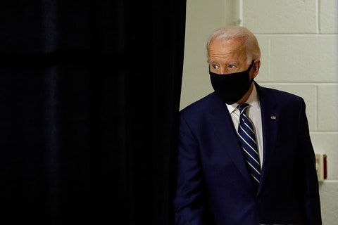 Joe Biden walking out from a stage curtain wearing a face mask