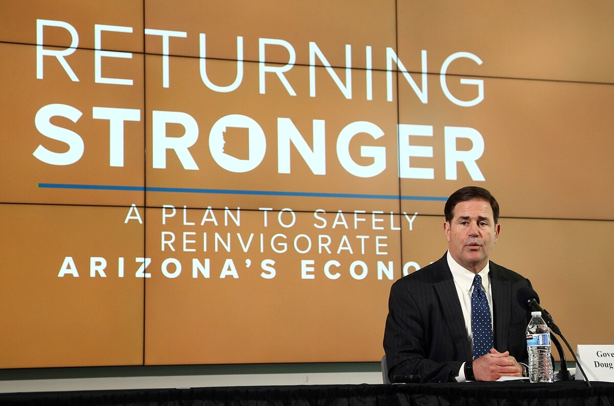 "Ducey sitting in front of sign that says ""Returning Stronger"""