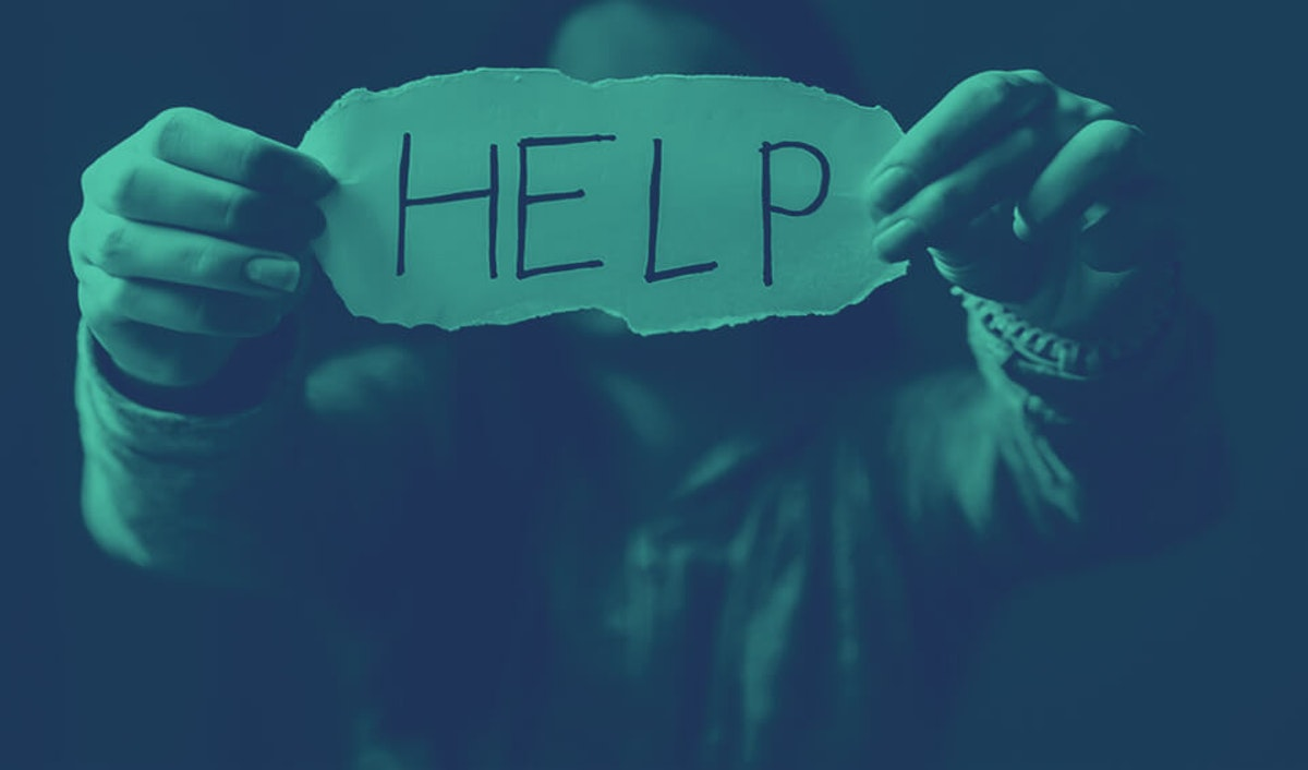 """woman holding sign that says """"help"""""""
