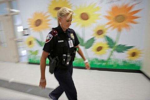 school resource officer walking down school hallway