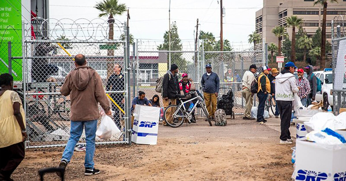 People gather in an empty lot near the Human Services Campus in downtown Phoenix.