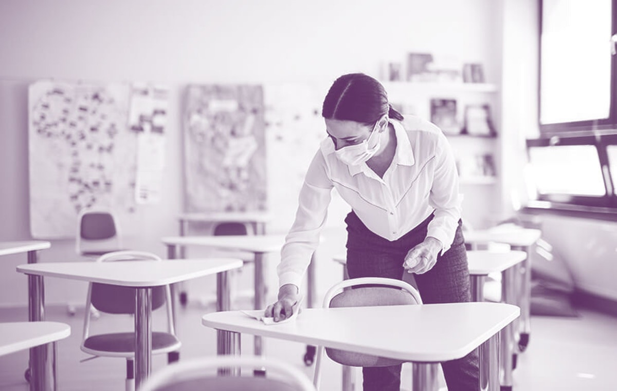 woman wearing face masks cleans a desk in a classroom