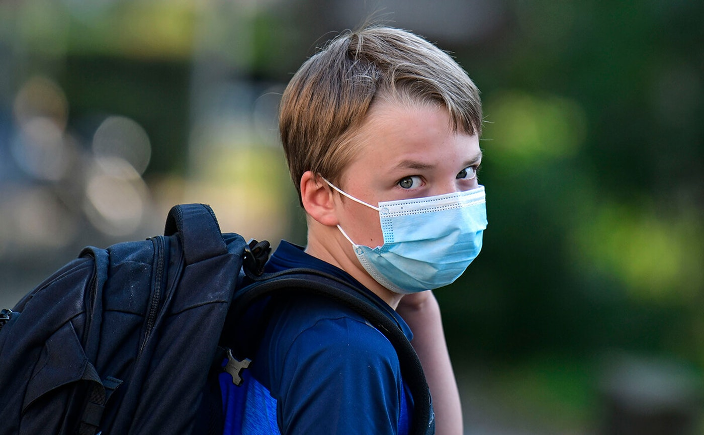 child looking at camera wearing face mask and backpack