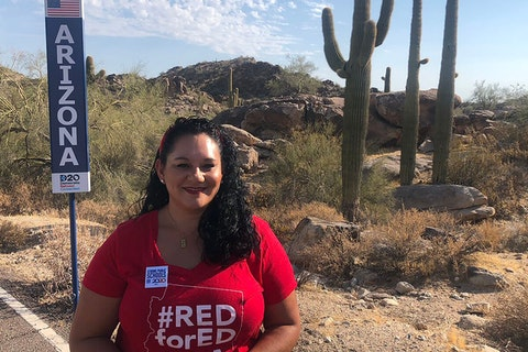 Marisol Garcia standing with Arizona signpost in front of desert landscape