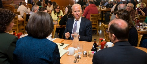 Joe Biden talking to a man and a woman at a restaurant table