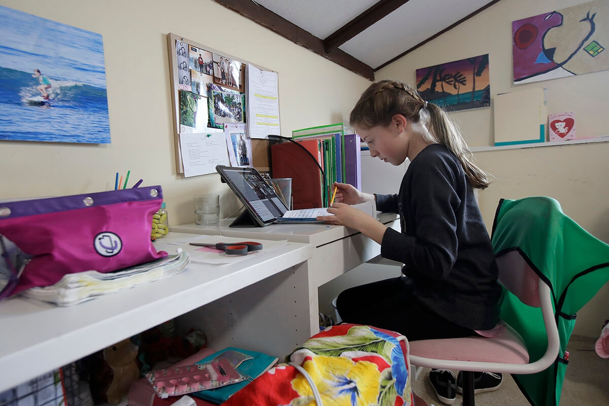 child working on her laptop at desk in her bedroom